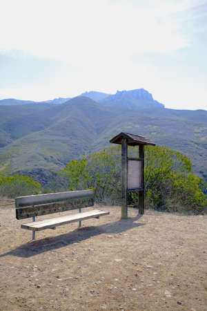 Kiosk and bench at entrance to hiking trail.