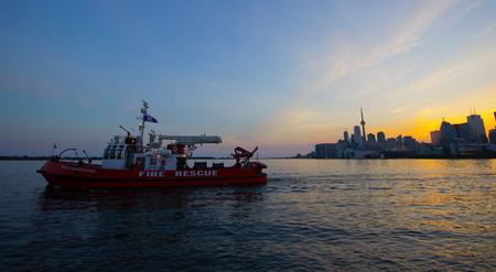 Fire rescue ships past photographers enjoying a beautiful sunset