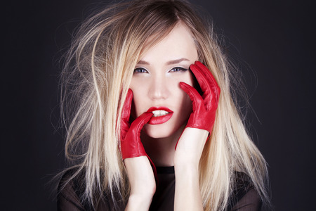 Fashion studio photo of beautiful blonde with red gloves