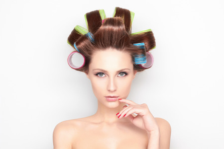 Beautiful young Woman with color curler. Haircare Girl