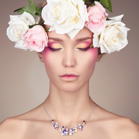 Young woman with flowers crown. Beauty model girl.Beautiful Girl with flowers on her head.Professional make-up