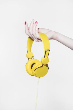 yellow headphones in the hand.music concept