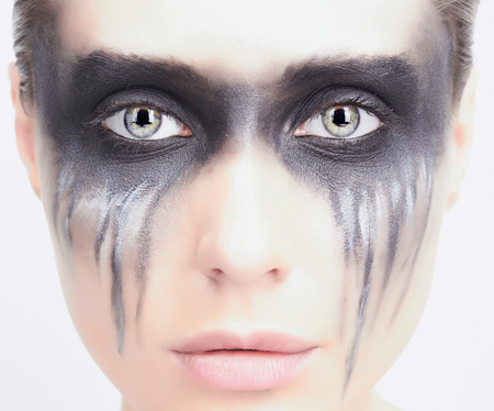 fashion close-up portrait of beautiful young woman.demon girl.oil make-up.isolated over white background.punks no dead Stock Photo