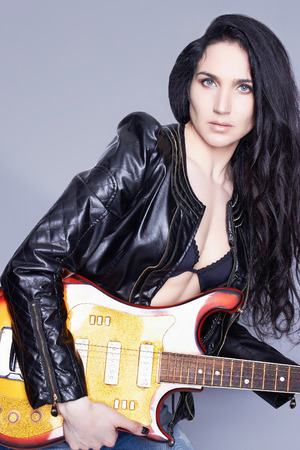 jacked: beautiful young woman with electric guitar.sexy girl in leather.rock music Stock Photo