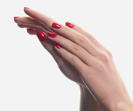 closeup of hands of a young woman with red manicure on nails against white background