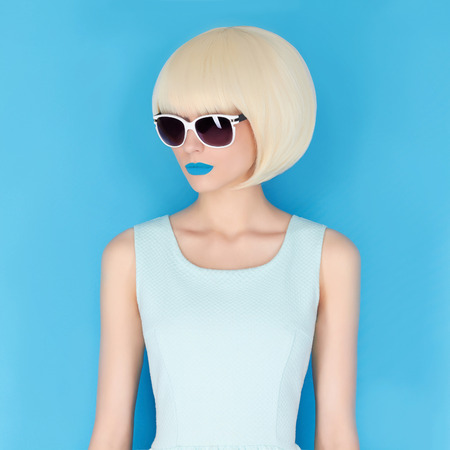 beautiful young woman in sunglasses. blue lips. bob hairstyle girl.blue background Foto de archivo