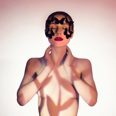 jeune fille adolescente nue: portrait d'une femme avec un papillon. Banque d'images