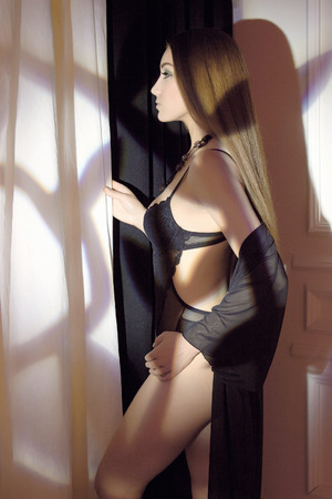 big boobs: Retrato de moda de Bello cuerpo mujer joven en ropa interior cerca de la ventana. Muchacha de la belleza atractiva en ropa interior negro Foto de archivo