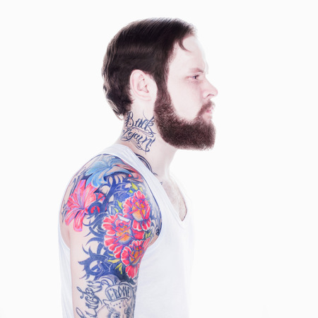 portarit: studio portarit of a fashionable young hipster man, tatooed and posing over a white background.long beard and mustache man