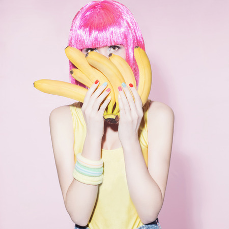 beauty young woman with pink bob hairstyle.Beautiful girl with bananas.healthy food concept Stok Fotoğraf