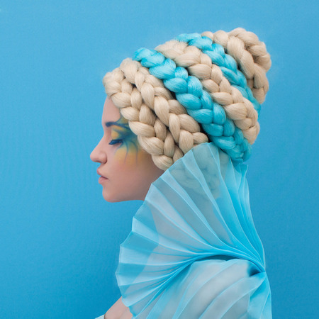 queen blue: beautiful woman with unusual hairstyle. Ocean queen. Blue background.painting face