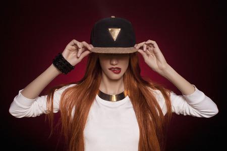 modelos posando: Mujer de hip-hop en la tapa con el pelo largo de color rojo. Retrato de muchacha moderna en el casquillo Foto de archivo