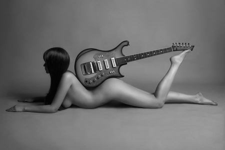 fashion girl style: beautiful young  woman with guitar. musical girl.fashion monocrome portrait