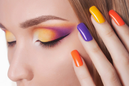Blond woman with manicure.Beautiful girl model with make-up and color nails.Nail design
