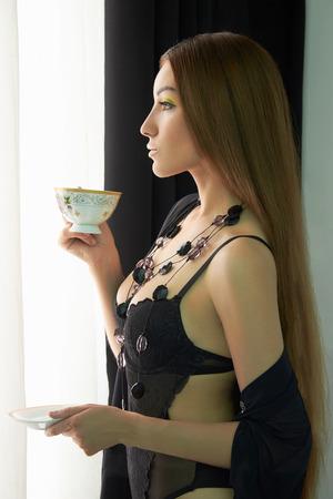 big boobs: fashion portrait of Beautiful body young woman in lingerie near the window. Sexy girl in black underwear drinking a tea Foto de archivo
