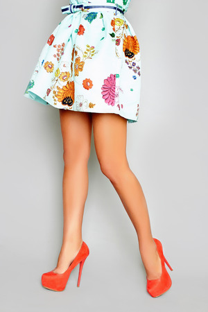 beautiful female legs in a skirt and heels.Young woman standing on one leg wearing high heels Standard-Bild
