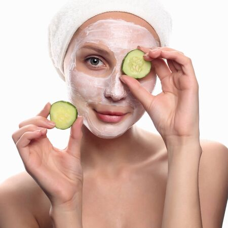 funny young woman with a face pack.cucumber mask.girl with cosmetic cream on a cheek.Skin care concept