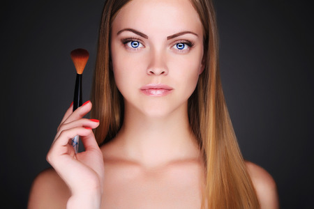 beautiful girl doing make-up.Young woman with blue eyes.Cosmetic.Applying Make-up