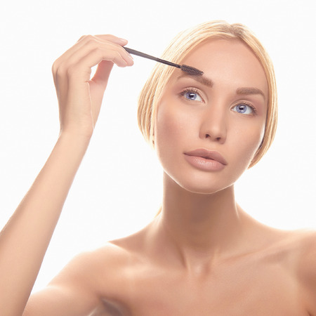blonde close up: young blonde woman make-up.girl Cosmetic. Base for Perfect Make-up.Applying Make-up