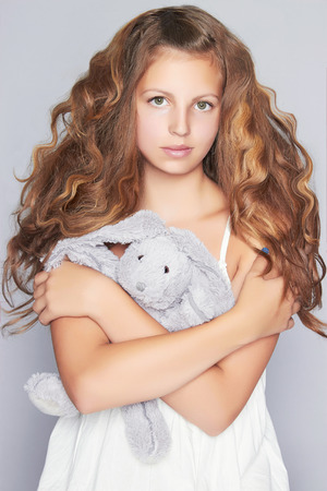 12 13: beautiful teen girl with soft toy.close-up portrait of teenager girl with long healthy hair Stock Photo
