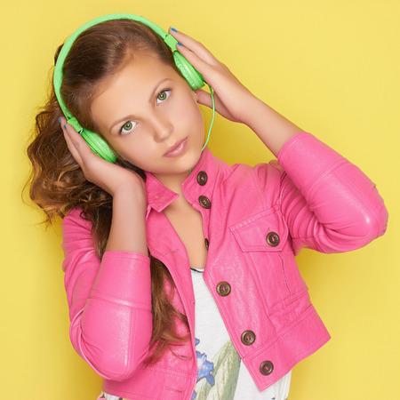 skin art: teen girl in pink leather wear listening music on headphones.beautiful young girl.Green headphones Stock Photo