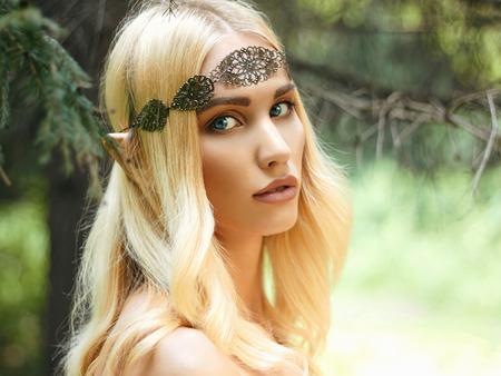 fantasy makeup: hermosa chica orejas de elfo. fantasía mujer joven en el bosque