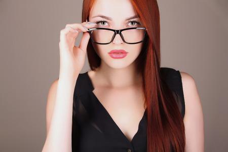 patron: bella mujer de negocios en copas. profesora sexy con el pelo rojo Foto de archivo