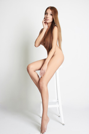 sexy topless girl: nude beautiful young woman sitting on a bar stool. sexy girl with long legs Stock Photo
