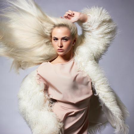 Beautiful blond young woman in fur.winter fashion.Beauty sexy Model Girl with healthy hair. Woman in Luxury Fur coat Foto de archivo