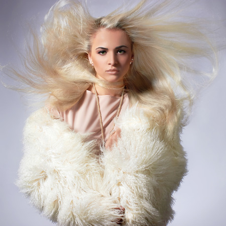 Beautiful blond young woman in fur.winter fashion.Beauty sexy Model Girl with healthy hair. Woman in Luxury Fur coat Stock Photo