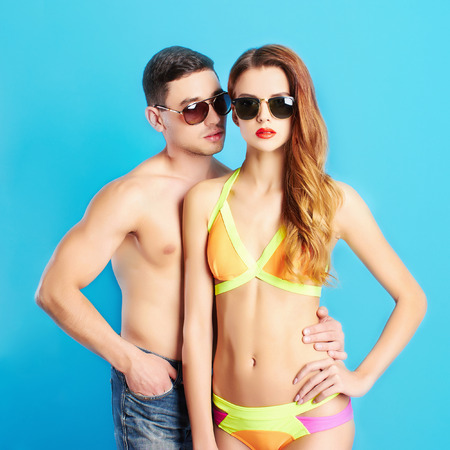 bikini couple: fashion beautiful couple in sunglasses.beauty woman and handsome man.boy and girl in bikini together
