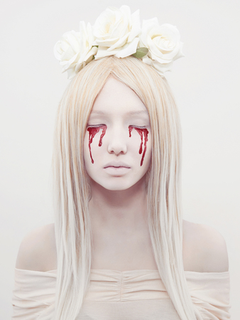 horror: beautiful young woman with blood from her eyes.blond sexy halloween girl.horror with flowers