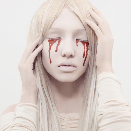 beautiful young woman with blood from her eyes.blond sexy halloween girl.horror
