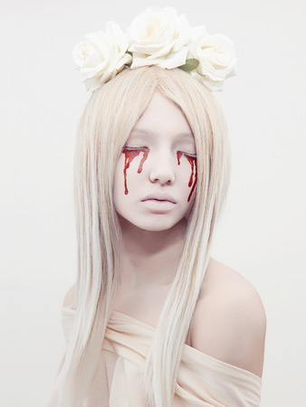 beautiful young woman with blood from her eyes.blond sexy halloween girl.horror with flowers