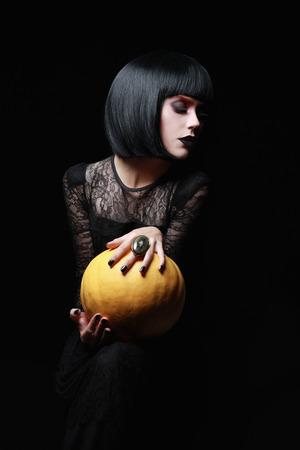 性的なブルネット魔女ハロウィーンの夜。ボブヘアとゴシック様式の女性。カボチャの少女