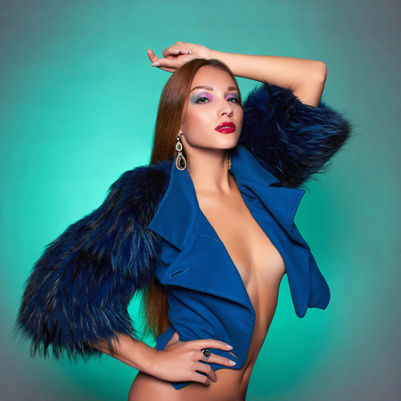 sexy glamour: Beautiful young woman in blue fur.winter fashion.Beauty sexy Model Girl with healthy hair. Woman in Luxury Fur coat and jewelry