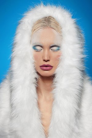 winter girl in fur.halloween snow queen.beautiful blond young woman.iced make-up Stock Photo