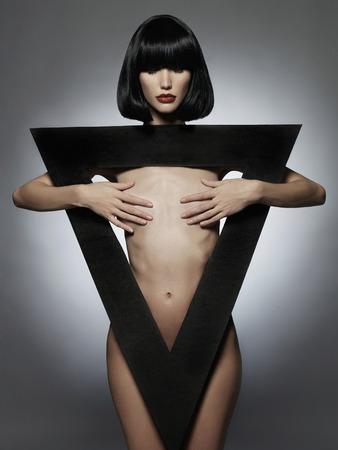 modelo desnuda: joven y bella mujer sexual con el retrato triangle.fashion negro de la chica desnuda en una geom�tricas labios rojos figure.big Foto de archivo