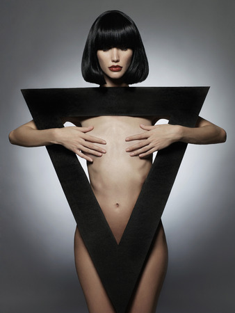 young nude girl: sexuellen schöne junge Frau mit schwarzen triangle.fashion Portrait des nackten Mädchens in einem geometrischen figure.big roten Lippen Lizenzfreie Bilder