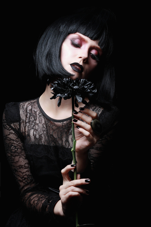 gothic girl: beautiful goth girl.black flower in hand of young woman.halloween concept.gothic make-up