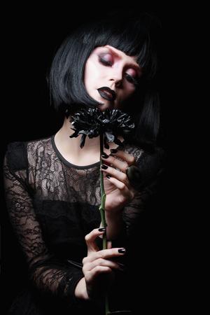 schöne Blume goth girl.black in der Hand der jungen woman.halloween concept.gothic Make-up Standard-Bild