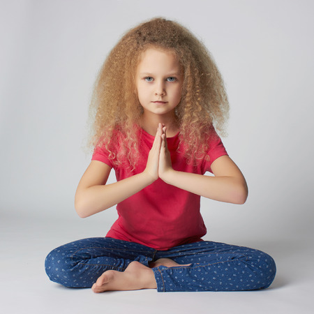 Relaxed child practicing yoga isolated on white background. little girl does yoga Foto de archivo