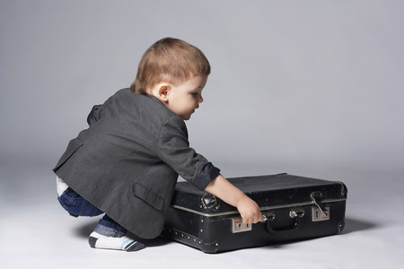 cute young boy: happy child with suitcases. stylish little boy.2 years old