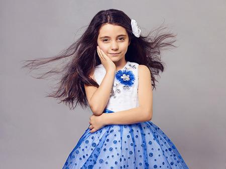 fashion portrait of beautiful little girl with flower in her hair.pretty little funny child.princess dress