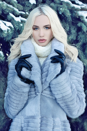 leather woman: Beauty model in winter forest. beautiful young Woman in fashionable Fur Coat and leather gloves. siberian luxury stylish blond girl