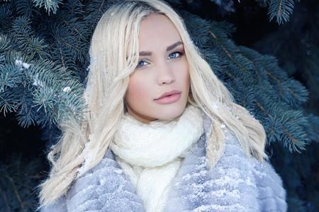 冬の森の美しさモード端。ファッショナブルな毛皮のコートと革手袋で美しい若い女性。髪に雪します。