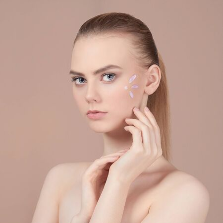 beauty young woman cares for face skin.beautiful girl with cosmetic cream on a clean fresh face. Skin care concept
