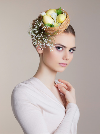 Spring Woman. Beauty model girl with Easter Hair Style. Beautiful Lady with easter eggs on her head. Easter Woman.Portrait of Beautiful Model with Colorful Eggs Stockfoto