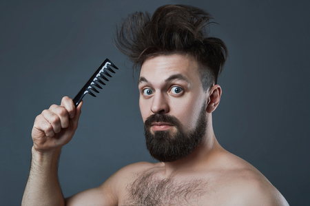 funny bearded man: funny fashion Portrait of bearded man with comb.Shaggy handsome boy.barber concept