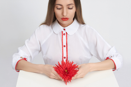 beautiful young woman with red flower. beauty girl in white room